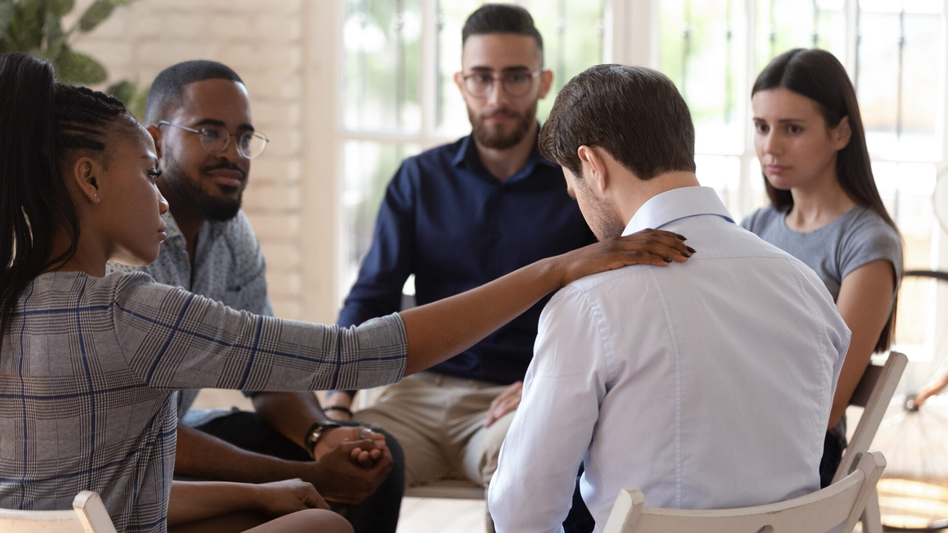 Rear view at upset man feel pain depression problem addiction get psychological support of counselor therapist coach diverse people friend group help patient during therapy counseling session concept.